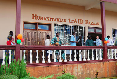 "A tour group outside the Humanitarian trAID Bazaar with local musical artist Roman ""Romeo"" Luks"