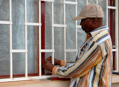 Napoleon covers the windows of the Total Health Center with plastic to block the dust of the dry season.