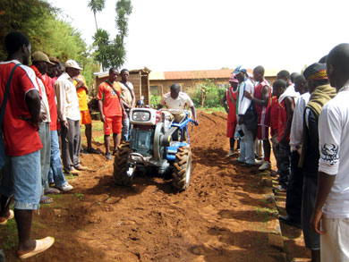 Farmers and students watch as Energy Farming technician Collins Litika demonstrates a tiller.