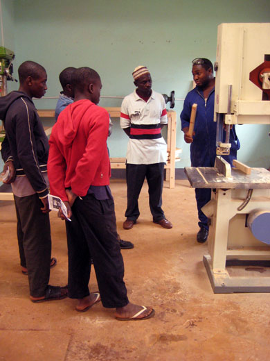 Victor, one of the Carpentry & Construction students, explains the various uses of the band saw, which is an entirely new tool in Kumbo.