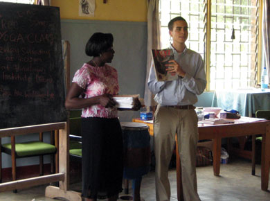 HIC volunteer John Daskovsky presents yoga books to class instructor Juliette Fai.