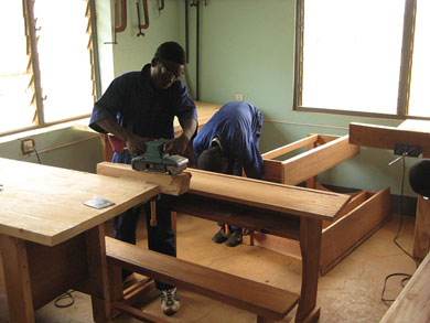 A student practices using a hand belt sander during the first practicum on wood finishing techniques.