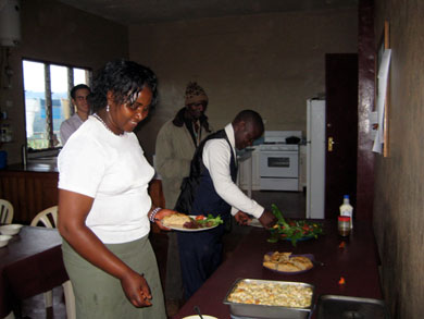 At a dinner prepared by residents to honor the house staff, head cook Vivian Lukong, housekeeper Gisleng Folaven and Guard Francis enjoy salad made from the garden's first harvest: green and red lettuce, tomatoes and edible calendula flowers.