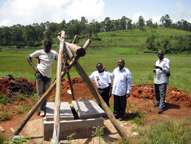 Energy Farming technicians Collins Litika and Albert Manjoh pose beside the completed well with rural engineer Visi Edwin and a local well technician.