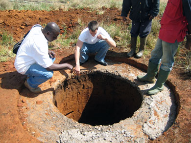 HIC volunteer Jeff Abella and rural engineer Visi Edwin examine the well's depth. Now finished, the hand-dug well reaches 9 meters, with standing water at a minimum of 3m, even at the height of the dry season.